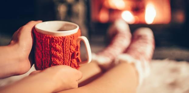 Herbst-Ideen: Herbst-Ideen: Frau sitzt mit Tasse Tee vor dem Kamin