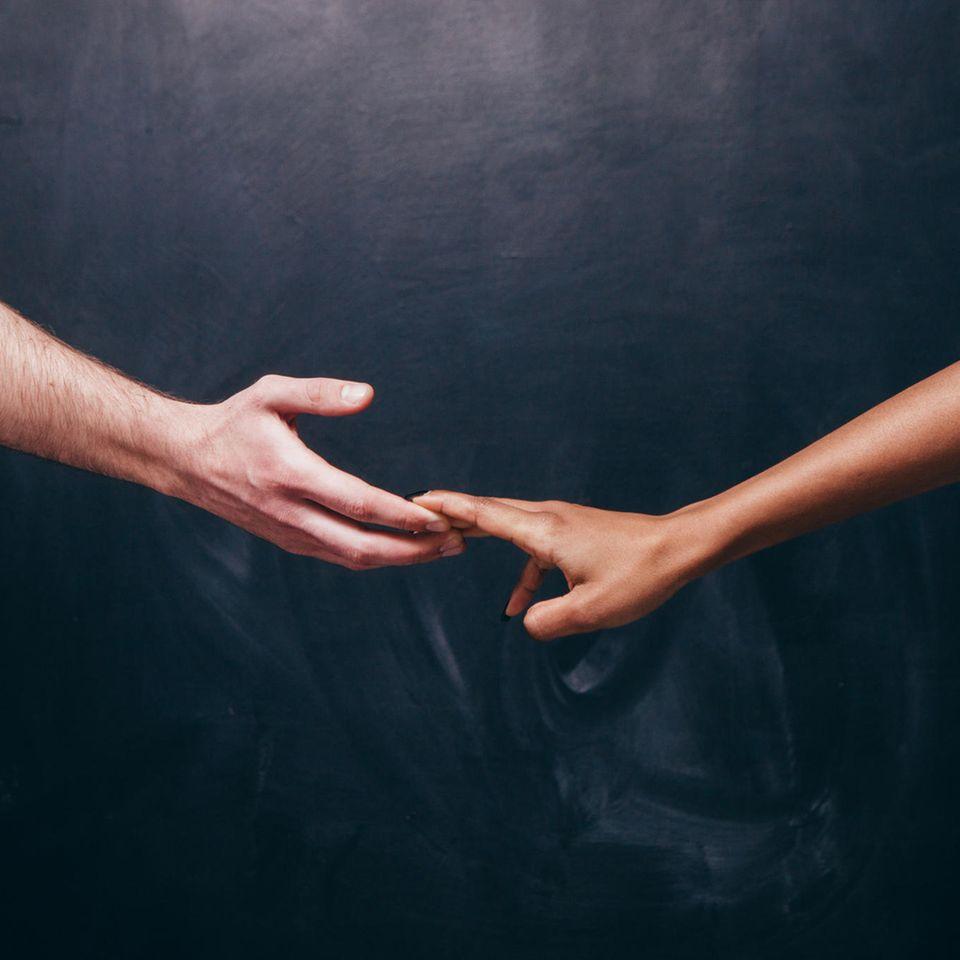 Trennungsschmerz: Eine Frauenhand und eine Männerhand, die sich voneinander weg bewegen