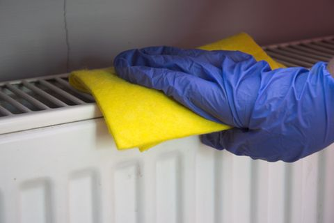 Heizkörper reinigen: Frau wischt Heizung ab