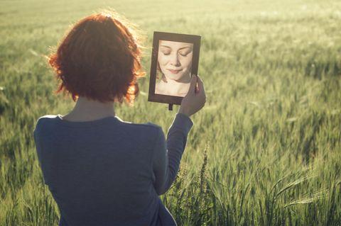 Bin ich schön? Eine Frau auf einer Wiese schaut in den Spiegel