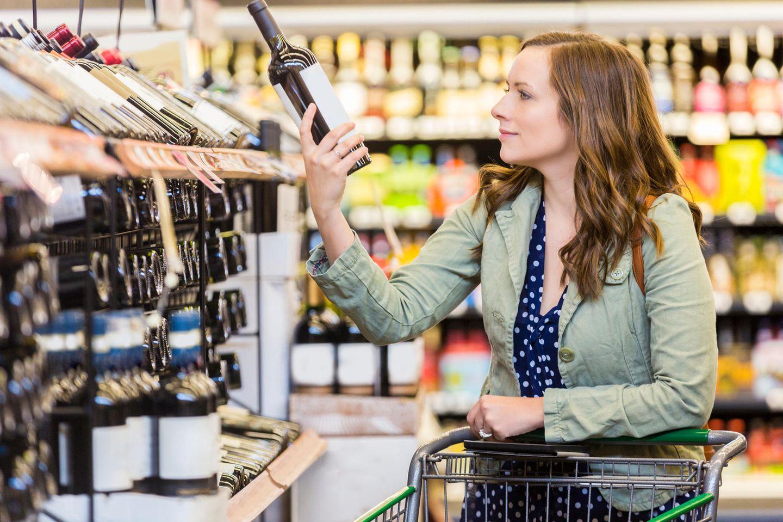 Frau kauft Rotwein in Supermarkt