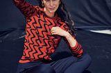 Sitzende Frau mit orange gemustertem Pullover