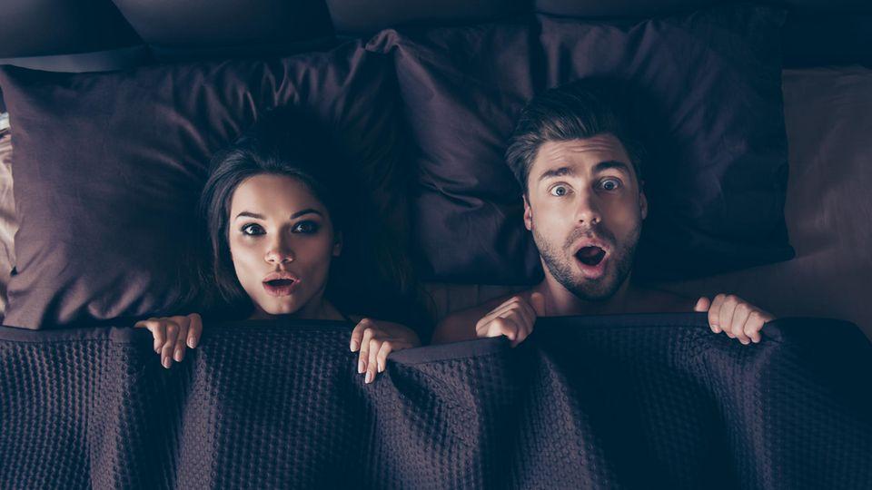 Überraschtes Paar im Bett