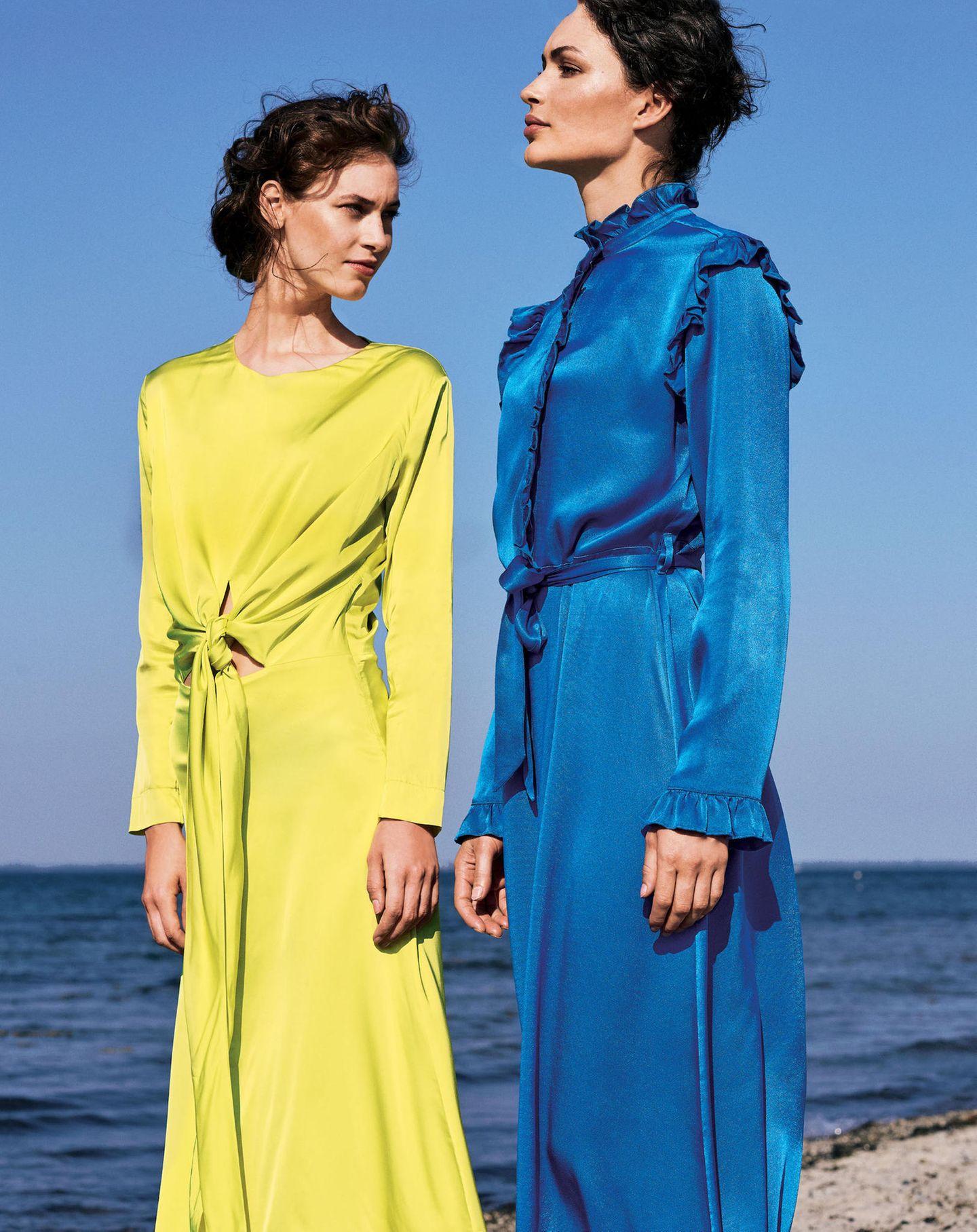 Zwei Frauen mit Kleidern aus Satin in blau und gelb