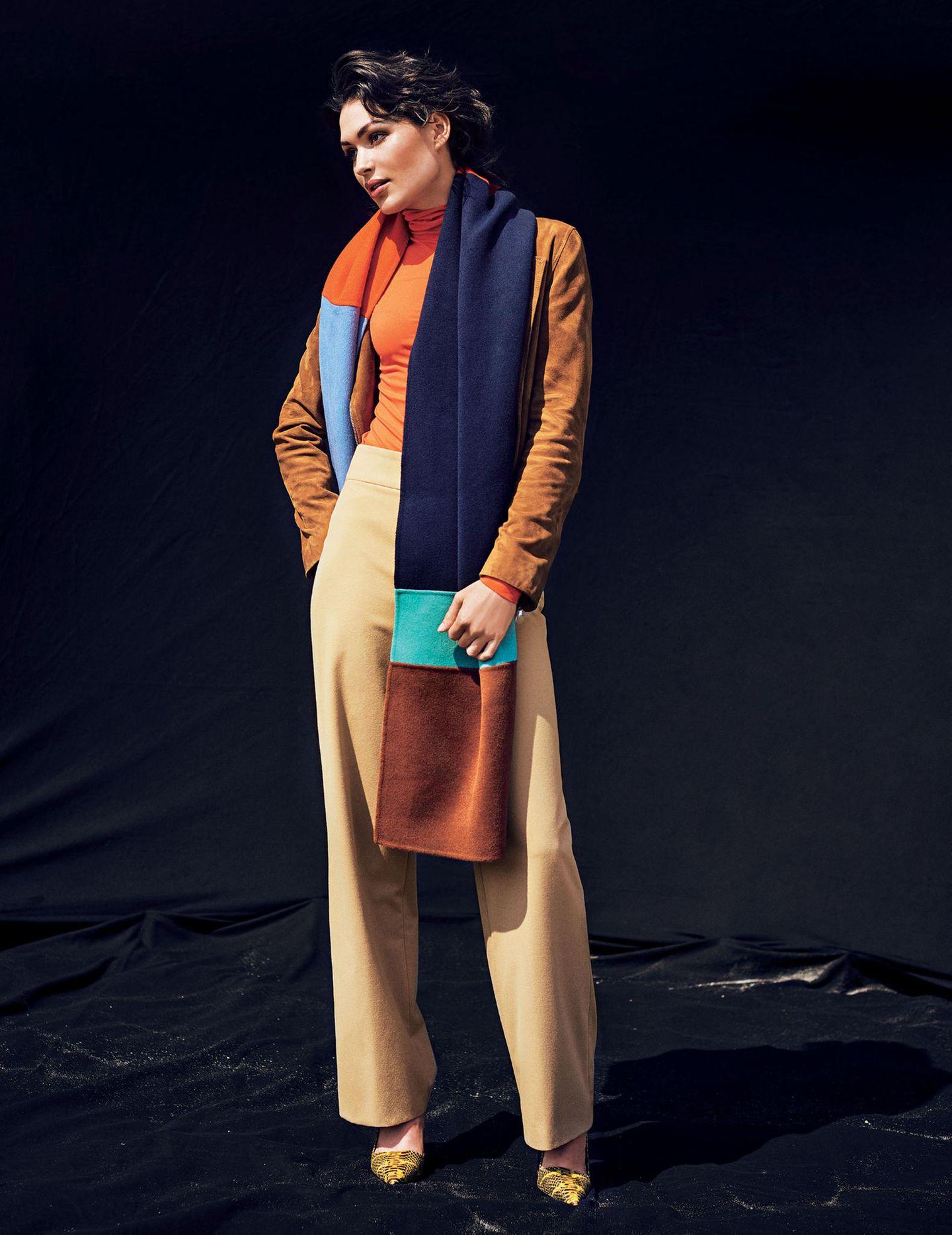 Frau trägt camelfarbenen Mantel und bunten Schal