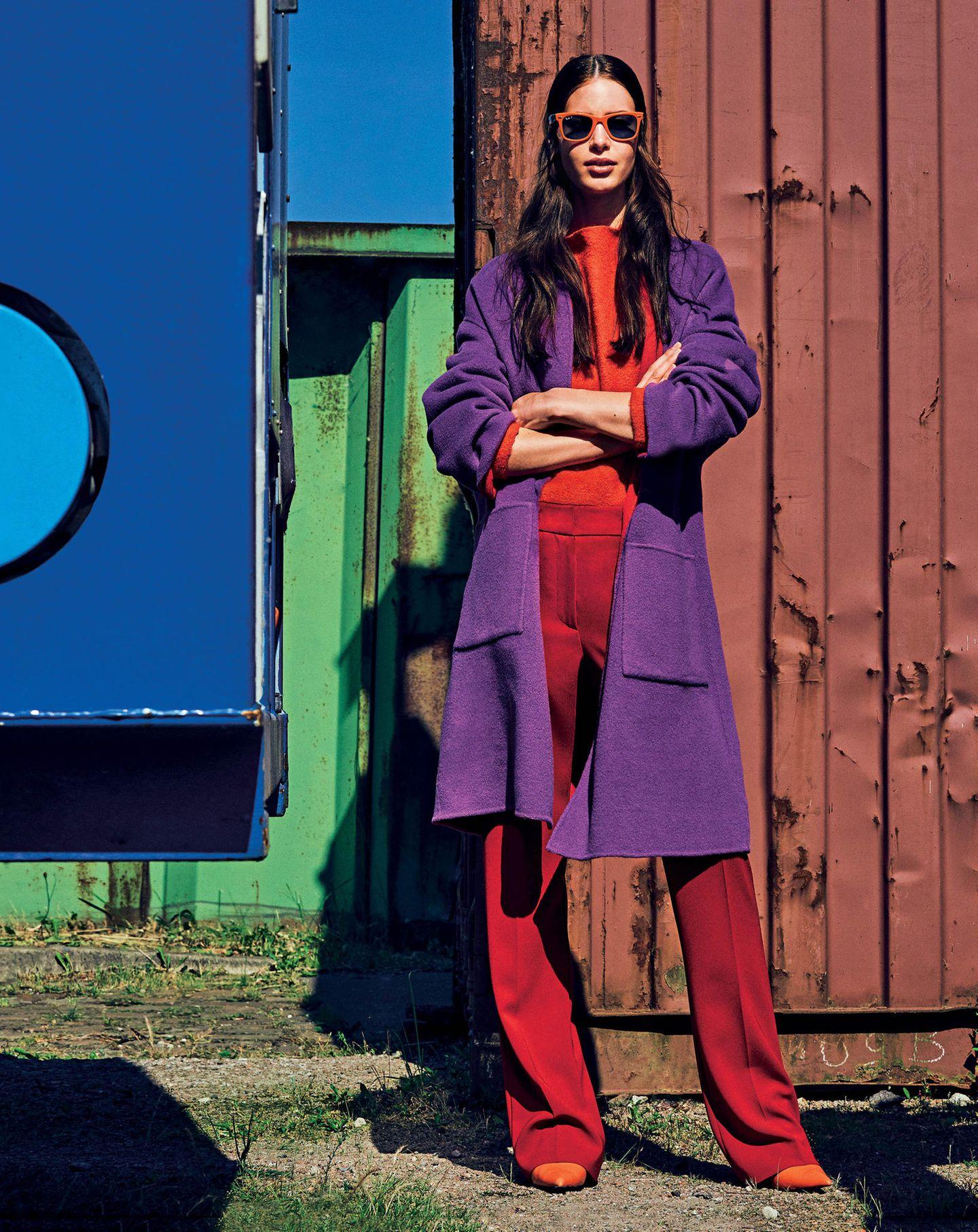 Frau trägt rotes Outfit mit violettem Mantel darüber