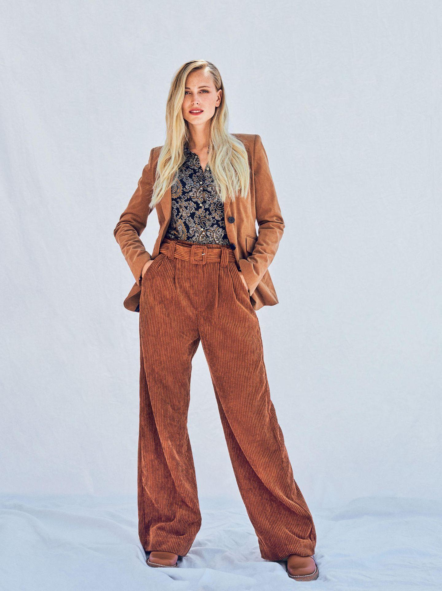Frau trägt weite Cordhose und Bluse mit Paisleymuster