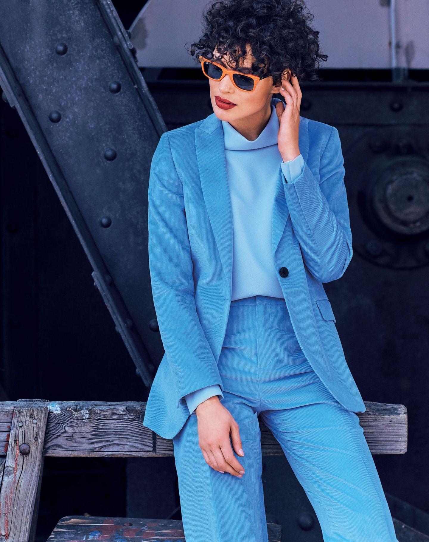 Frau in blauem Cord-Anzug