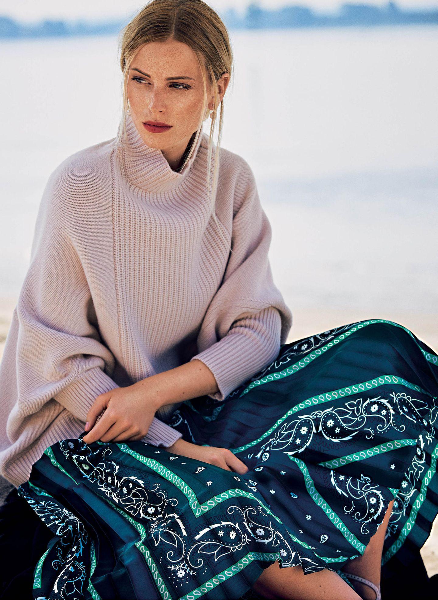 Sitzende Frau mit Plissee-Rock in blauem Muster
