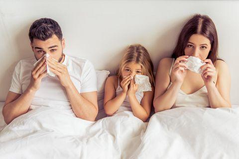 Dauererkältung: Kranke Familie im Bett