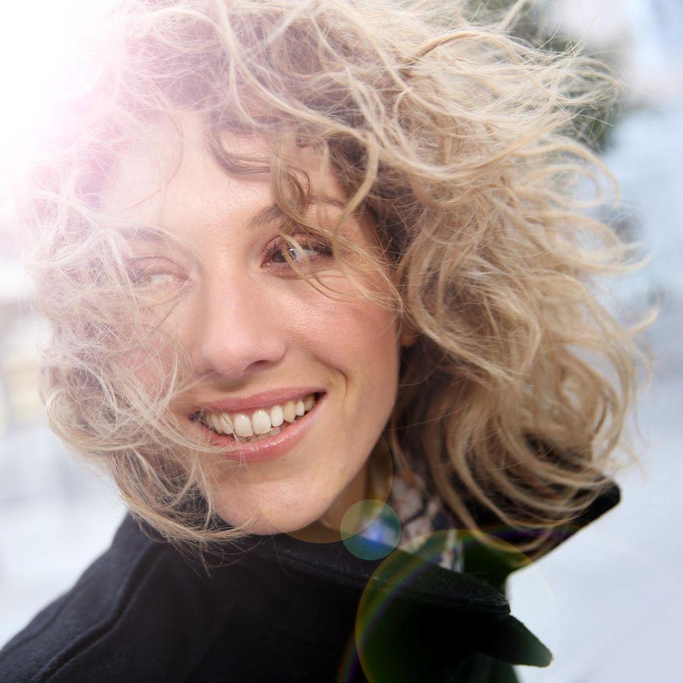 Lachende Frau mit wehenden Haaren