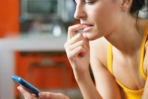 Angst vorm Telefonieren: Frau schaut auf Handy