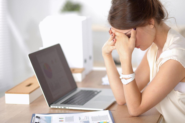 Vitamin B12 Mangel: Müde Frau am Schreibtisch