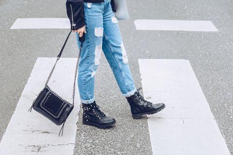 Kleidungsstücke, die man Secondhand shoppen sollte: Frau mit zerrissener Jeans und Lederboots