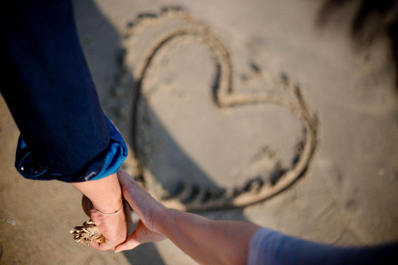 Was Männer wollen: Frauenhand greift Männerhand über einem Herz im Sand