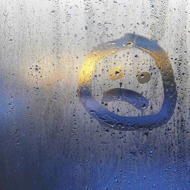 Kondenswasser am Fenster: Frau wischt Fenster
