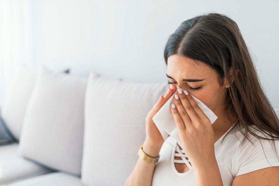 Chronischer Schnupfen: Frau putzt sich die Nase