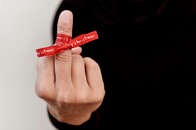 Ich hasse Weihnachten: Stinkefinger mit umgebundener roter Weihnachtsschleife