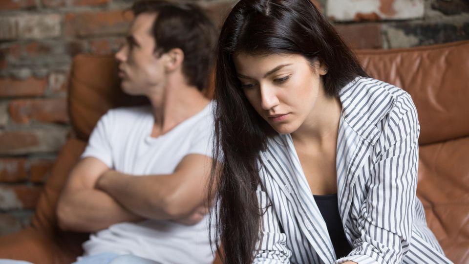 Beziehung am Ende: Frau schaut traurig zu Boden, Mann beleidigt woanders hin