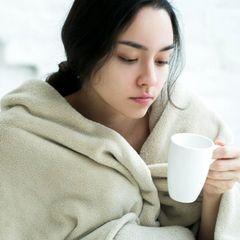 Schüttelfrost: Frierende Frau mit Tee