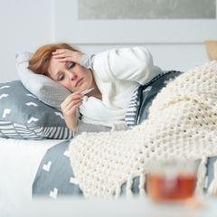 Fieber senken: Frau mit Fieberthermometer