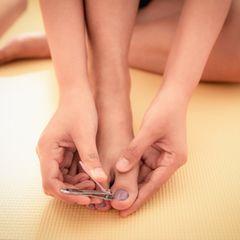 Fußnägel schneiden: Frau schneidet sich die Fußnägel