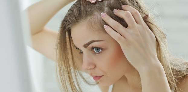 Empfindliche Kopfhaut: Frau schaut Kopfhaut an