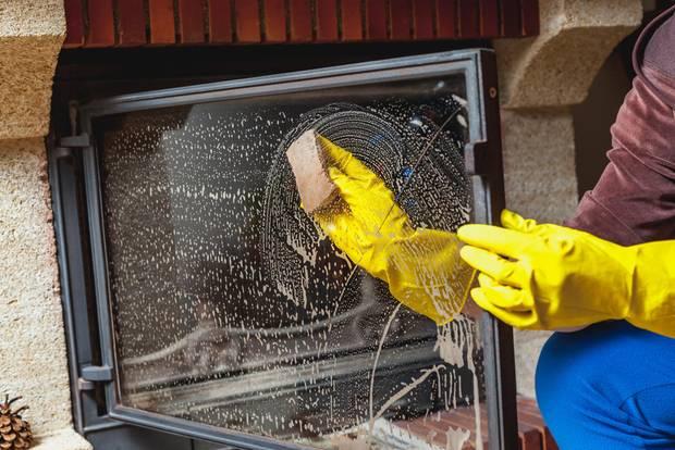 Kamin reinigen - Frau putzt Kaminscheibe