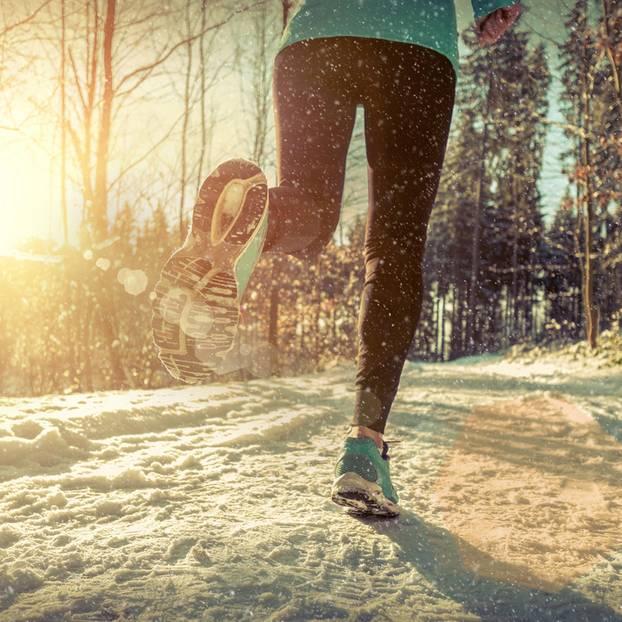 Joggen im Winter: Eine Frau joggt über einen schneebedeckten Waldweg