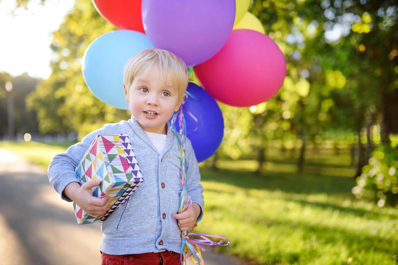 Kindergeburtstagsgeschenke: Kleiner Junge mit Geschenk und Luftballons