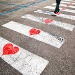Warum verliebt man sich? Ein Mensch geht über einen Zebrastreifen mit Herzen