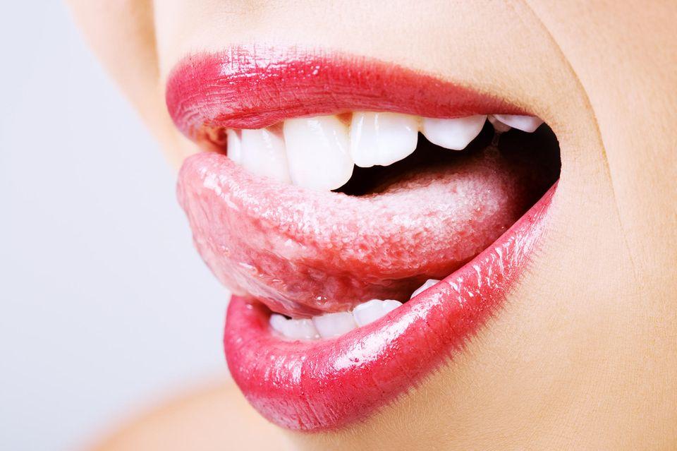 Pickel auf der Zunge: Frau streicht mit Zunge über die Zähne