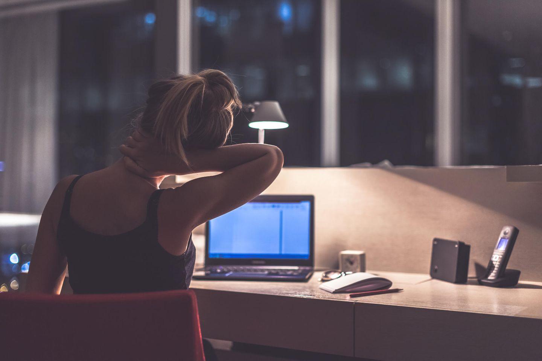 Burnout vermeiden: Müde Frau sitzt am Laptop