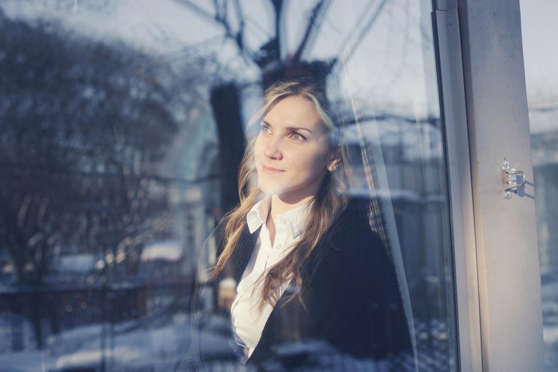 Mit Mitte 30 das Leben ändern: Nachdenkliche junge Frau am Fenster