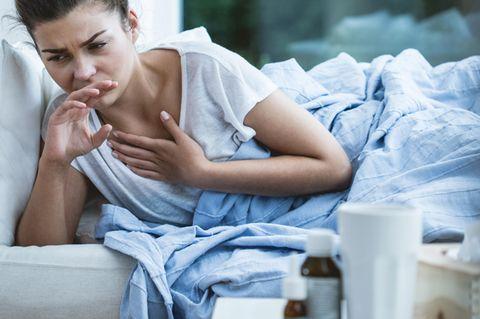 Schmerzen beim Husten – Frau hustet im Bett