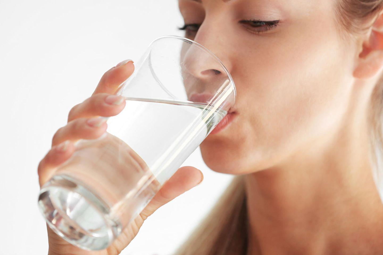 Schluckauf: Frau trinkt Wasser aus einem Glas