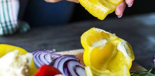 Gesünder essen durch Selbstmanipulation: Frau schneidet Paprika