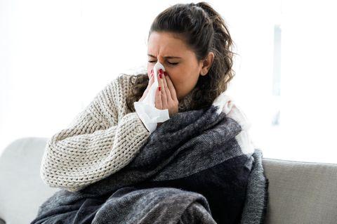 Gelber Schnupfen: Frau putzt sich die Nase