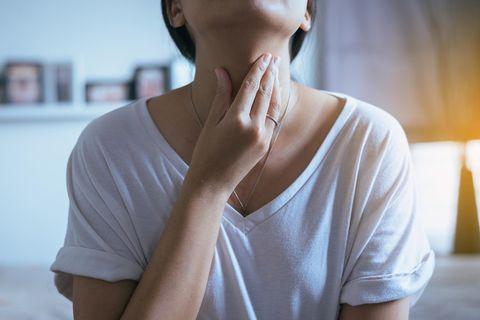 Einseitige Halsschmerzen – Frau fasst sich an den Hals