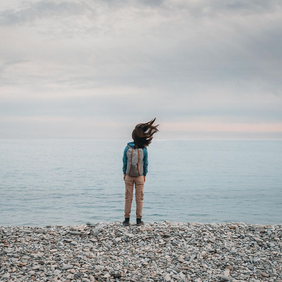 Wetterfühligkeit: Frau steht am Meer, Wind zerzaust die Haare