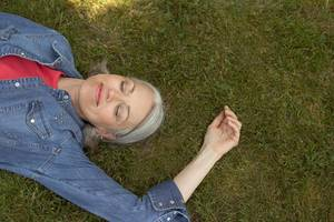 Diese eine Angewohnheit lässt dich länger leben! Frau auf Rasen liegend