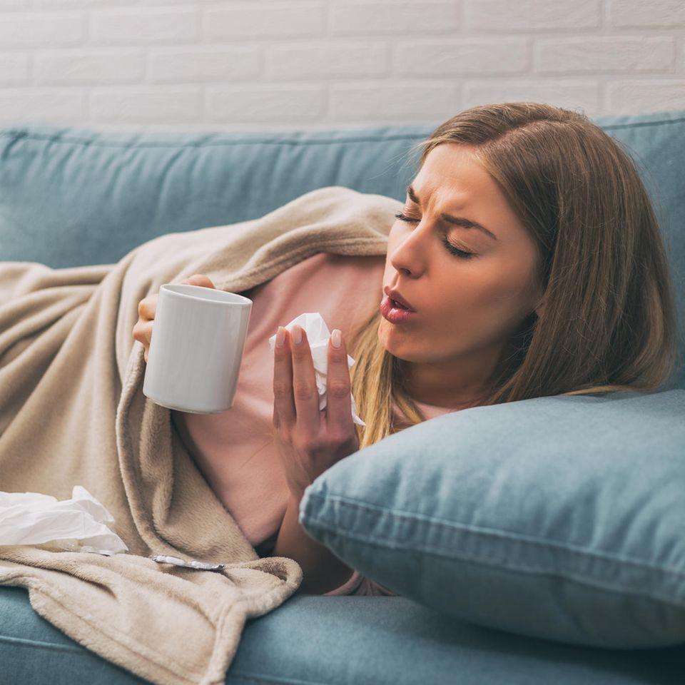 Chronischer Husten: Frau hustet auf der Couch