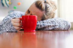 Was hilft gegen Kater? Frau mit schmerzverzerrtem Gesicht liegt auf dem Tisch und hält eine Tasse in der Hand