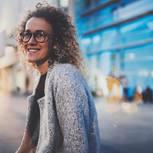 Authentisch sein: Eine lächelnde lockige Frau mit Brille vor einem modernen Bürogebäude