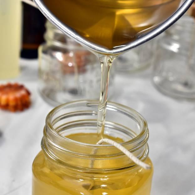 Kerzen gießen: Flüssiges Wachs wird in ein Glas gegossen