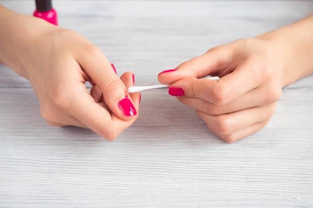 Maniküre-Fehler: Pinker Nagellack wird mit Wattestäbchen ausgebessert