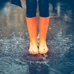 Durchblutung fördern: Frau mit Gummistiefeln im Regen
