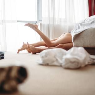 Der erste Sex: Pärchen auf dem Boden neben dem Bett beim Sex oder Petting