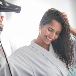 Kalt föhnen: Frau föhnt sich die Haare