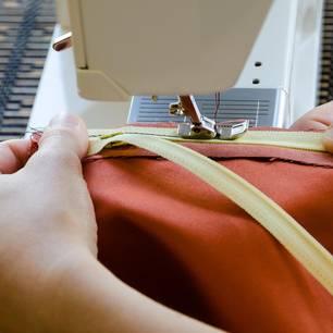 Reißverschluss reparieren: Frau näht an Maschine